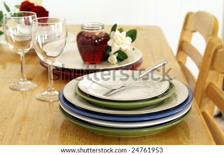 Stacked plates on a golden wood dinner table with chairs, wine glasses, candle and flowers