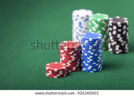 Stacked poker chips on green felt table.  Shallow depth of field with focus on front stack.