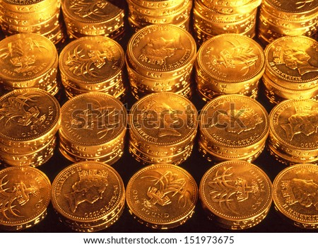 Stacked pound coins in organised regular rows under tungsten lighting to give a golden hue - stock photo