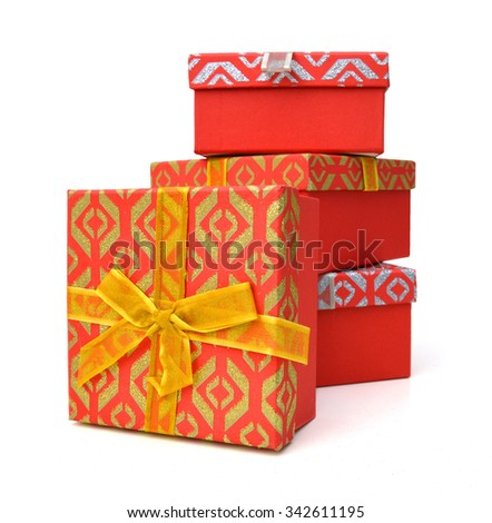 Stacked red Christmas gift boxes with ribbon and bow isolated on a white background