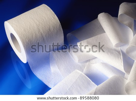stacked rolls of toilet paper on sky blue background - stock photo