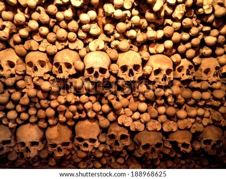 Stacked skulls and bones in czech church cemetery. - stock photo