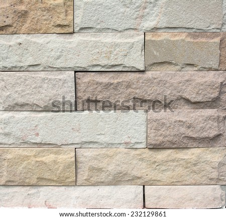 Stacked stone cladding building facade for background texture - stock photo