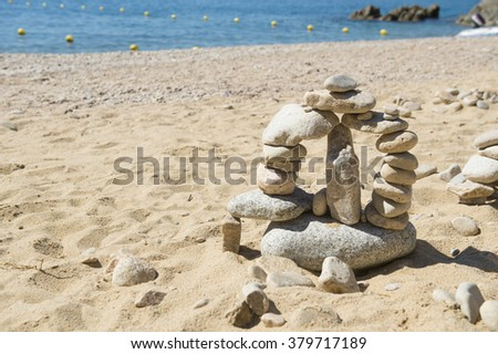 Stacked stones at the beach - stock photo
