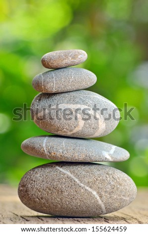 Stacked stones on a green natural background - stock photo