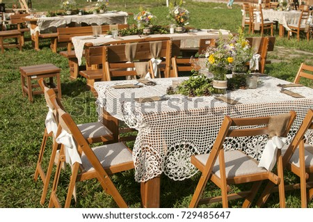 Stacked Tables For Guests For Rustic Outdoor Wedding Ceremony Of Green Lawn  In Countryside House Garden