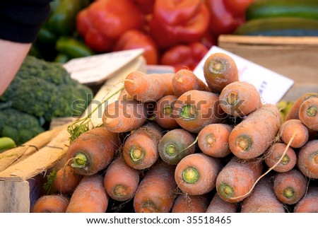 Stacked unwashed carrots for sale at a vegetable market