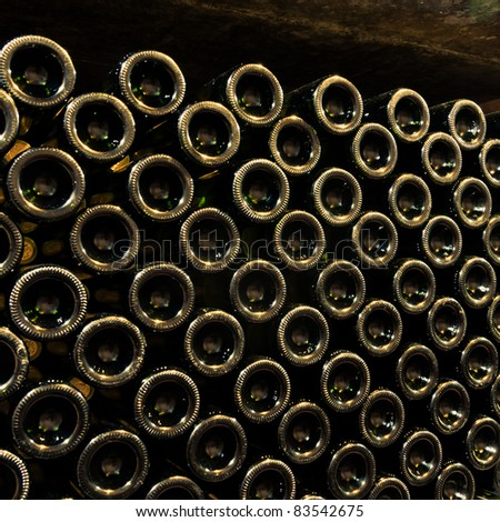 stacked up wine bottles in the cellar - stock photo