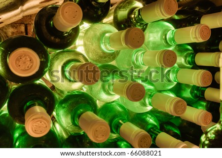 stacked up wine bottles in the wine cave - stock photo