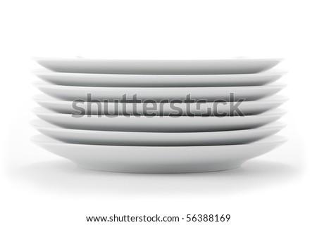 Stacked white dishes on seamless white background. - stock photo