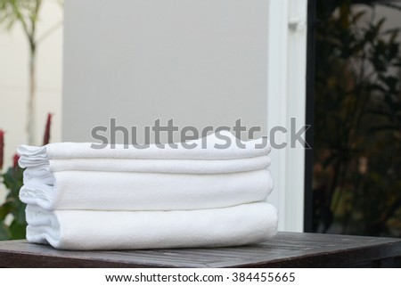 Stacked white spa cloth beach towels in garden background.  - stock photo