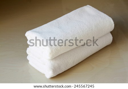 Stacked white spa cloth beach towels on marble  background.  - stock photo