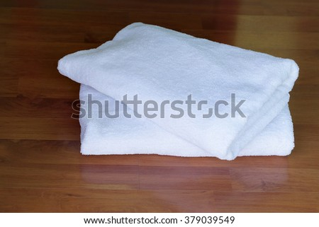 Stacked white spa cloth beach towels on wooden background.  - stock photo