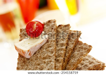 Stacked wholemeal crispbread with soft cheese and cherry tomato