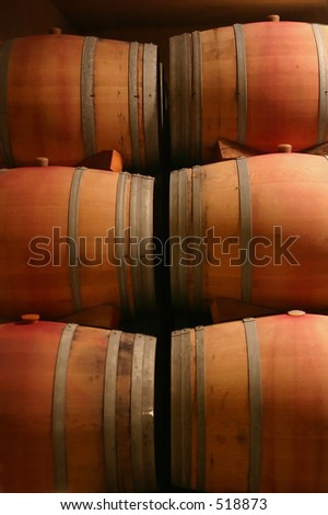 Stacked Wine barrels in wine cellar of napa winery... Low light conditions - stock photo