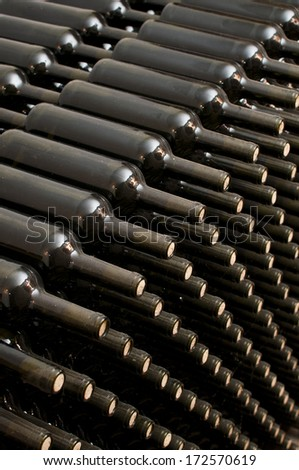 stacked wine bottles in the cellar - stock photo