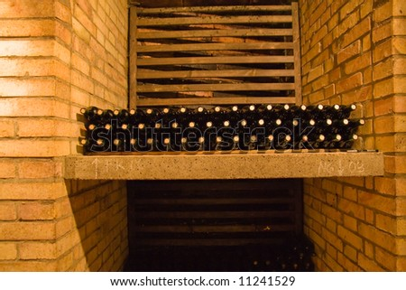 stacked wine bottles on the shelf - stock photo