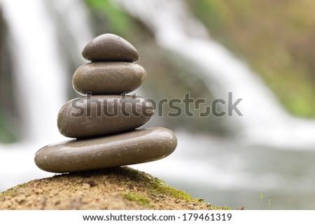 Stacked zen stones and waterfall - stock photo