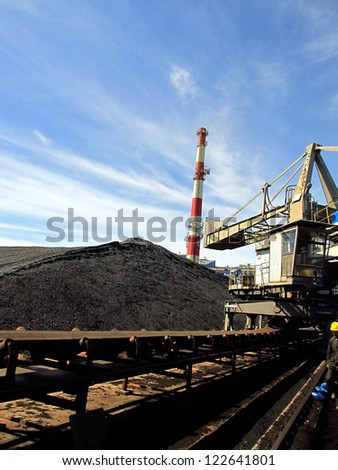 Stacker with a heap of coal next to the plant - stock photo