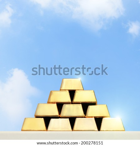 stacks and rows of gold ingots or golden bullion bars with sky background - stock photo