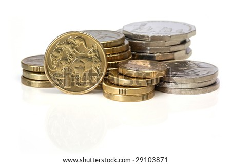 Stacks of Australian coins, reflected on white surface. - stock photo