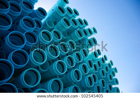 Stacks of blue PVC water pipes - stock photo