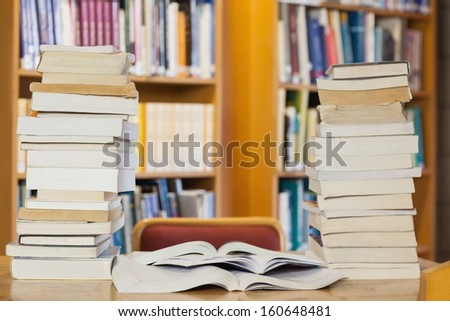Stacks of books on desk in library - stock photo