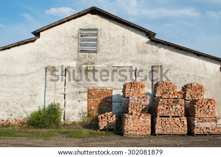 Stacks of bricks on wooden pallets near the old gray house - stock photo