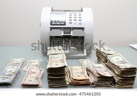 Stacks of cash next to a money counting machine.