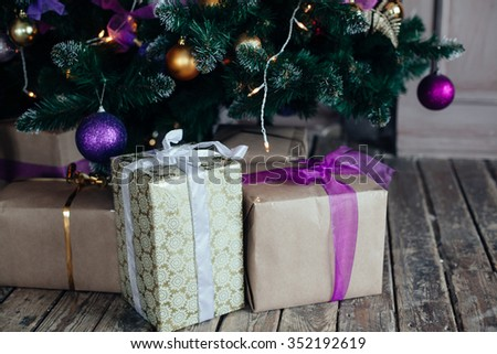 Stacks of Christmas presents under a Christmas tree with defocused lights - stock photo