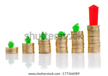 Stacks of coins, green and red home. Mortgage concept by money house from coins - stock photo