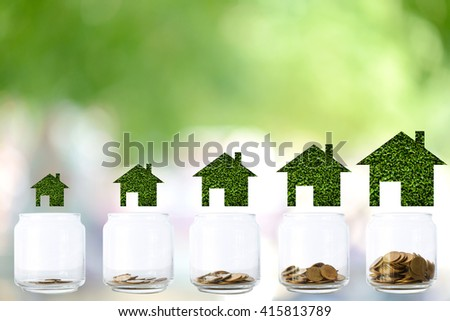 Stacks of  coins in  bottle on blur background,Concept  different size houses and stacks of coins - stock photo