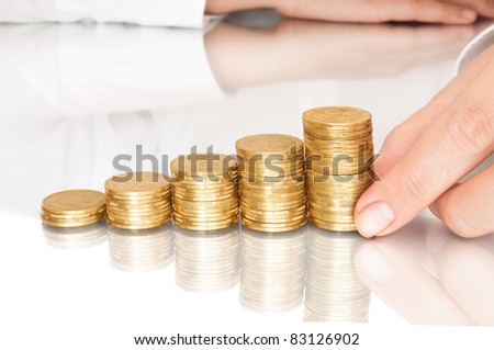 stacks of coins like diagram with reflection and hand put coins - stock photo