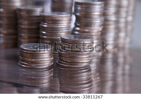 Stacks of coins on a table with reflections in the glass. Shallow depth of field focus on first stack of coins.