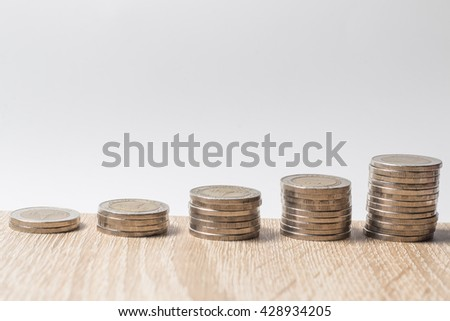 Stacks of coins on wood table - stock photo