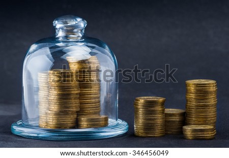stacks of coins protected under a glass dome  - stock photo