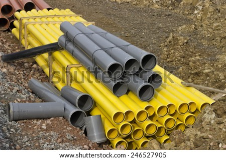 Stacks of colored pvc pipes at construction site. Selective focus. - stock photo