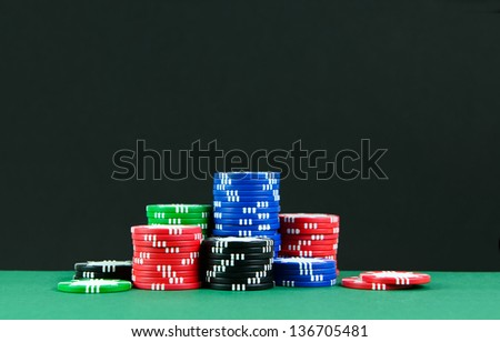 Stacks of colorful poker chips on gambling tables - stock photo