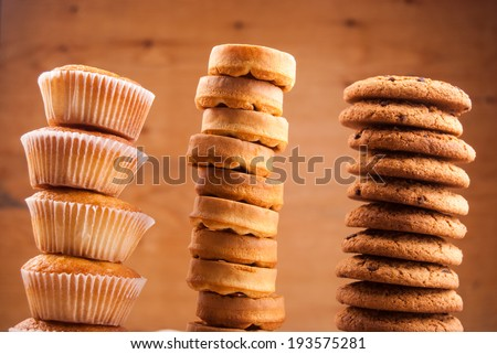 Stacks of cookies and cup against wood - stock photo