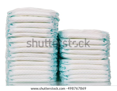Stacks of disposable diapers closeup isolated on white background.