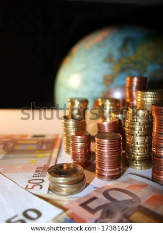 Stacks of Euro and Cent coins and some 50 Euro banknotes in front of a globe with Europe - stock photo