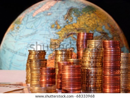 Stacks of Euro and Cent coins in front of a globe with Europe - stock photo