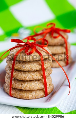 Stacks of gingerbread cookies tied with red ribbon on white plate - stock photo