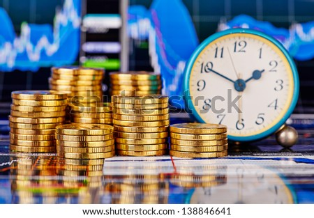 Stacks of golden coins, clock and the financial chart as background. Selective focus