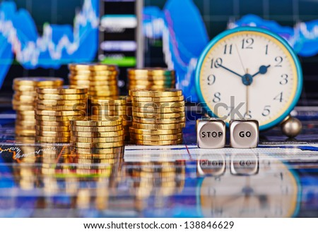 Stacks of golden coins, clock, dices cubes with the words STOP GO. The financial chart as background. Selective focus