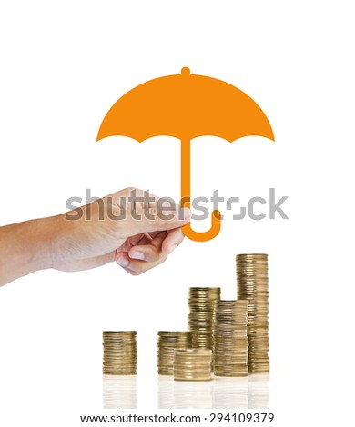 Stacks of golden coins covered by paper umbrella. insurance concept - stock photo