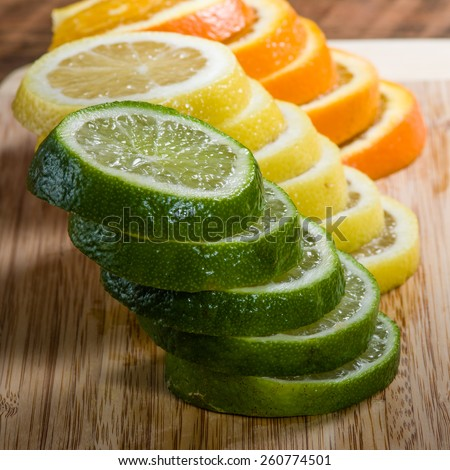 Stacks of lemon, lime and orange slices on cutting board - stock photo