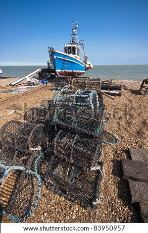 stacks of lobster pots on a shingle beach with a commercial fishing vessel in the background