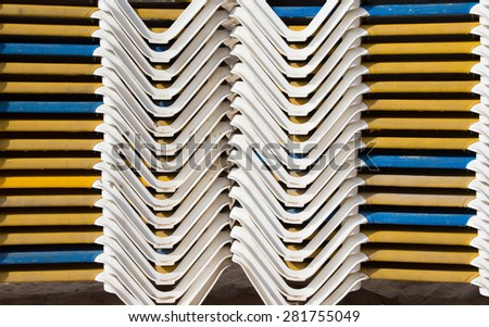 Stacks of loungers on a sandy beach. Estoril. Portugal. - stock photo