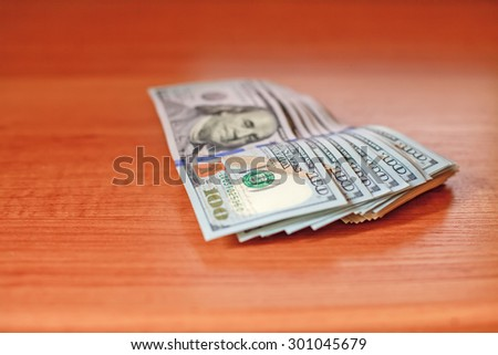 Stacks of one hundred dollars banknotes on wooden desk. Macro - stock photo